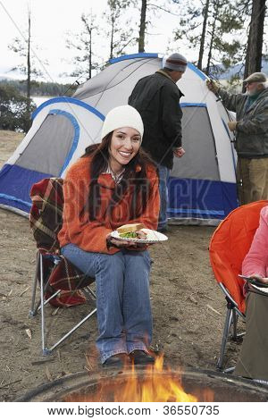 Happy woman having food at campfire with man at tent in background