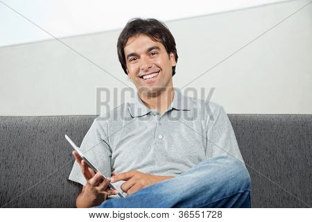 Portrait of happy young man in casual wear using digital tablet