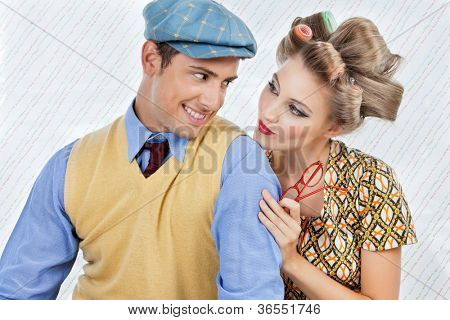 Retro styled young couple looking at each other over textured background