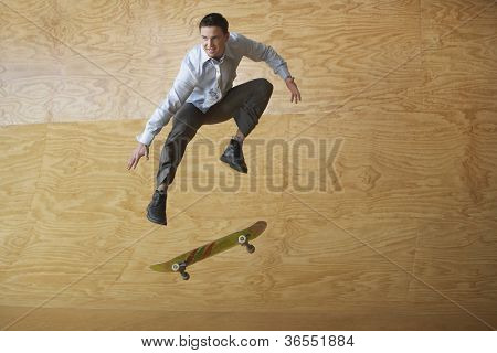 Businessman on skateboard in midair