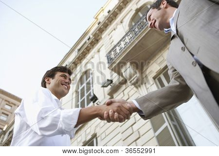 Two businessmen shaking hands for a successful deal with building in the background