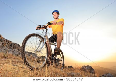 Person riding a mountain bike on a sunset, low angle view