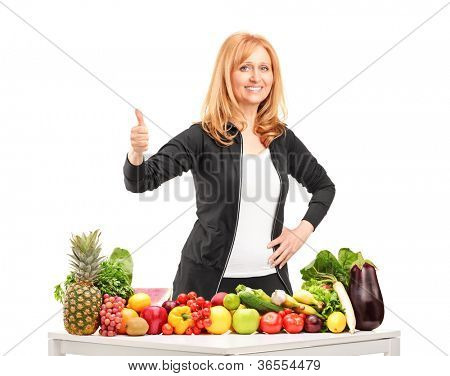 Woman with fruits and vegetables giving a thumb up isolated on white background
