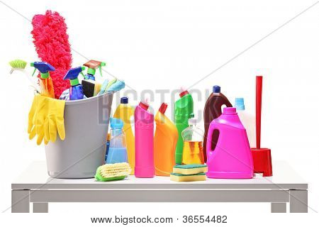 Bucket and cleaning supplies on a table isolated on white background