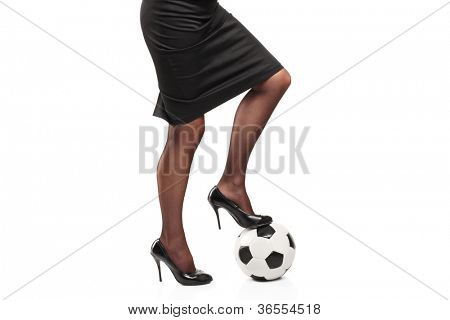 Woman in high heels standing on a soccer ball isolated on white background