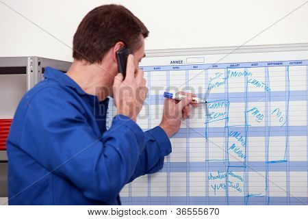 Man in blue overalls talking on the phone and writing on a board