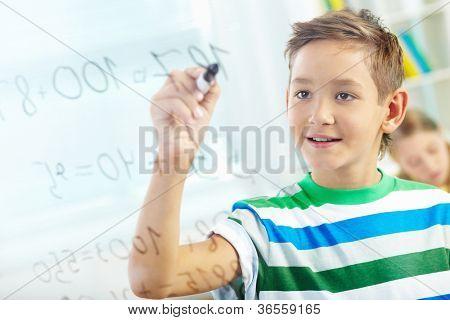 Retrato de guapo estudiante hacer sumas con compañero de clase en segundo plano