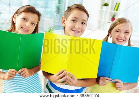 Portrait of happy classmates with books smiling at camera in classroom