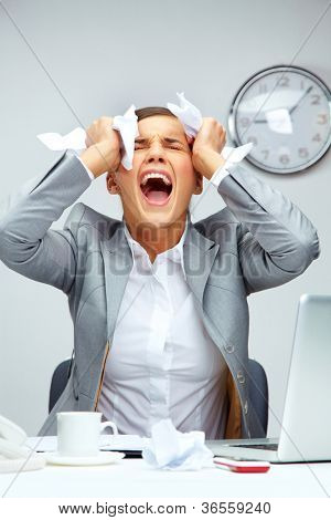 Image of young employer touching her head in frustration and crying at workplace