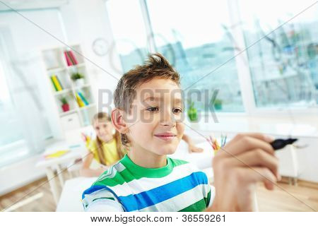 Portrait of clever boy doing sums on transparent board with schoolmate on background
