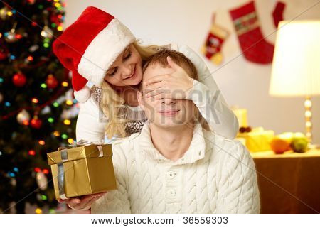 Portrait of happy woman closing male�?�¢??s eyes by her hands while holding giftbox in front of him