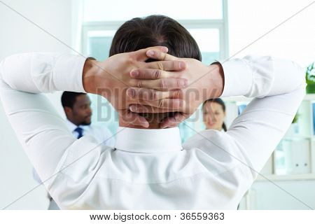 Back of successful business leader interacting with his colleagues