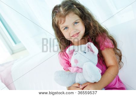Portrait of lovely girl with teddybear sitting on sofa at home