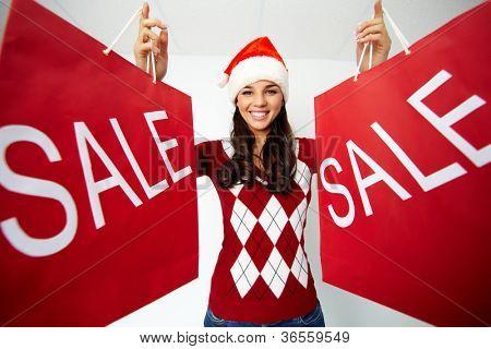 Menina feliz em cap Santa detém paperbags vermelho com símbolo de venda