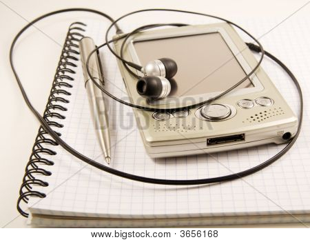Pen And Pda With Headphones On Spiral Notebook