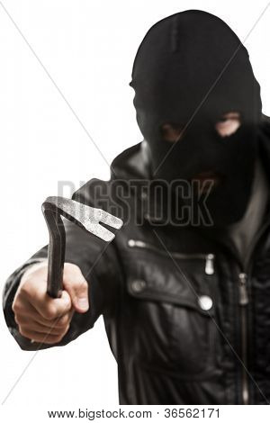Crime scene - criminal thief or burglar man in balaclava or mask covering face holding crowbar in hand for break opening home door lock