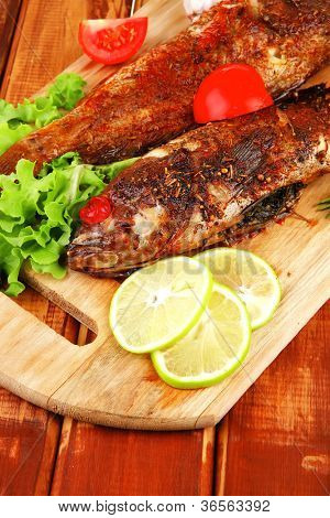 main portion of two grilled fish served on wooden table with castors