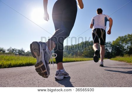 Young couple jogging in park at morning. Health and fitness.
