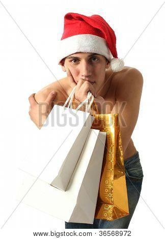 Junge muskulöse sexy Mann trägt einen Weihnachtsmann-Hut mit Kopie Raum Einkaufstüten isolated on white