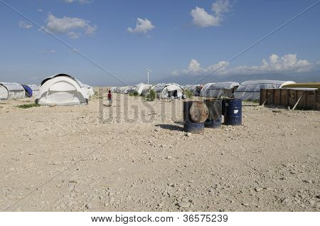 water containers in a haitian tent city.