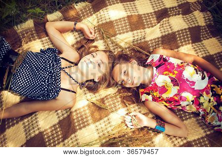 Two Girls Are Lying On The Cheked Spread