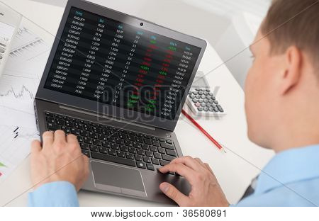 Business Man Analyzing The Stock Market On Laptop