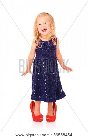 A portrait of a beautiful little girl in a blue dress and red too big heels smiling over white background
