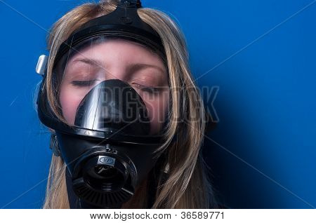 Woman in gasmask against dark background closeup