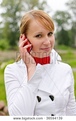 Young Pretty Girl Talking By Mobile Phone In The Park