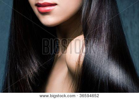 mujer con pelo negro largo brillante y el estudio de labios rojos tiro