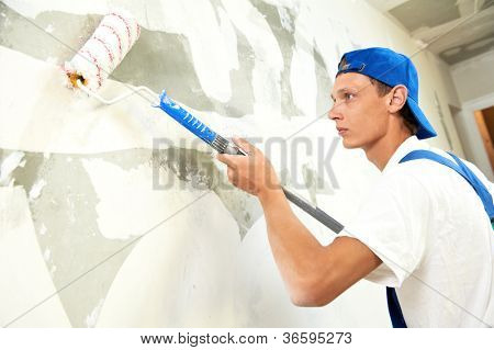 One painter with paint roller making wall prime coating  at home repair renovation work