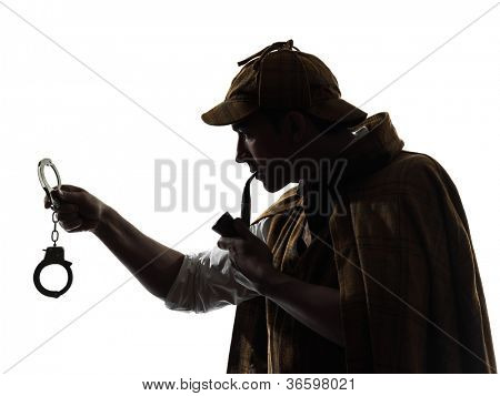 sherlock holmes holding handcuffs silhouette in studio on white background