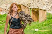 STARA LUBOVNA, SLOVAKIA - AUGUST 26: female falconer performing with eagle-owl bird during Falconry