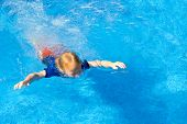 picture of wet pants  - Young boy learning to swim with his clothes on in a pool - JPG