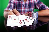 Cropped image of a winning four aces poker hand. green background