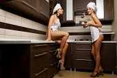 Two sexy housewives in kitchen room