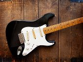pic of stratocaster  - Vintage black double cutaway guitar on old wood surface - JPG