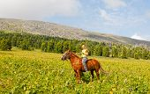 stock photo of bareback  - Happy girl riding a horse bareback at mountains - JPG