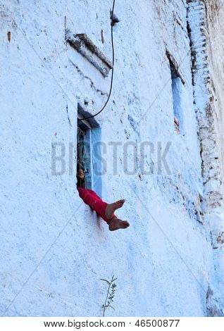 Child Sitting In a window. Morocco