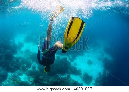 Freediver descending towards coral reef
