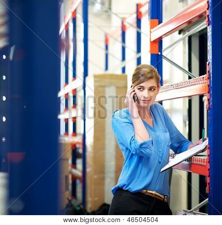 Female Logistics Employee On The Phone And Checking Inventory