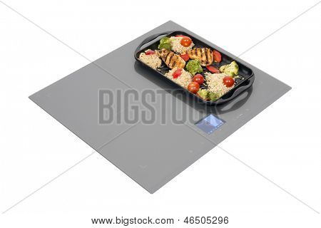 Grey glass induction hob with roast chicken isolated on white. Clipping path included.