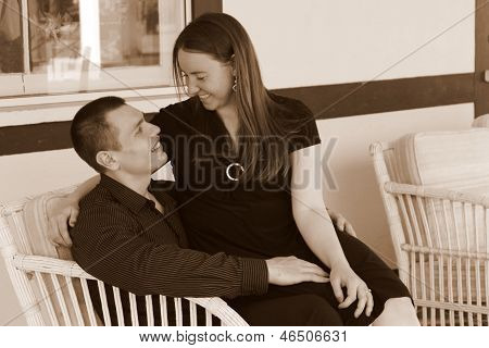 Young smiling couple sitting together on loveseat