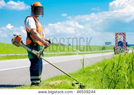 Road landscaper cutting grass