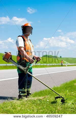 Road landscapers cutting grass
