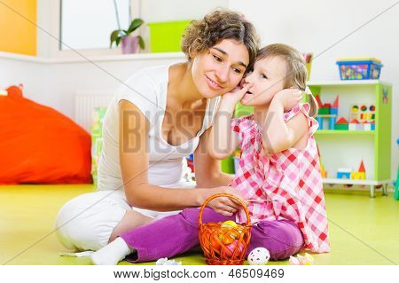 Young Mother And Little Daughter Painting Easter Eggs