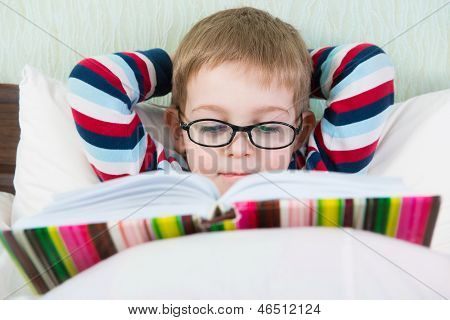 Little Cute Boy Reading Book In Bed