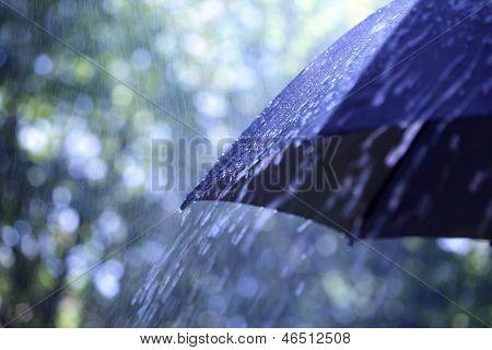 Regentropfen fallen von einem schwarzen Schirm
