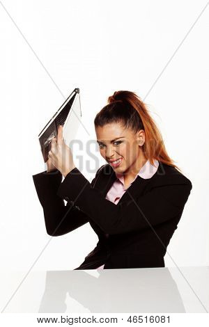 Angry businesswoman about to smash her laptop on the desk isolated on a white background