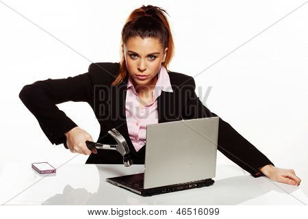 Angry businesswoman fixing her laptop with a hammer, holding it over the open keyboard while looking up at the camera